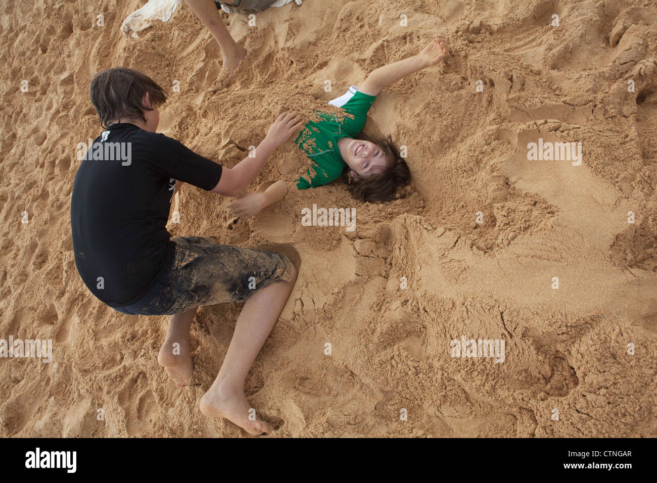 Older brother buries younger brother on a soft, sandy beach, Hawaii. - Stock Image