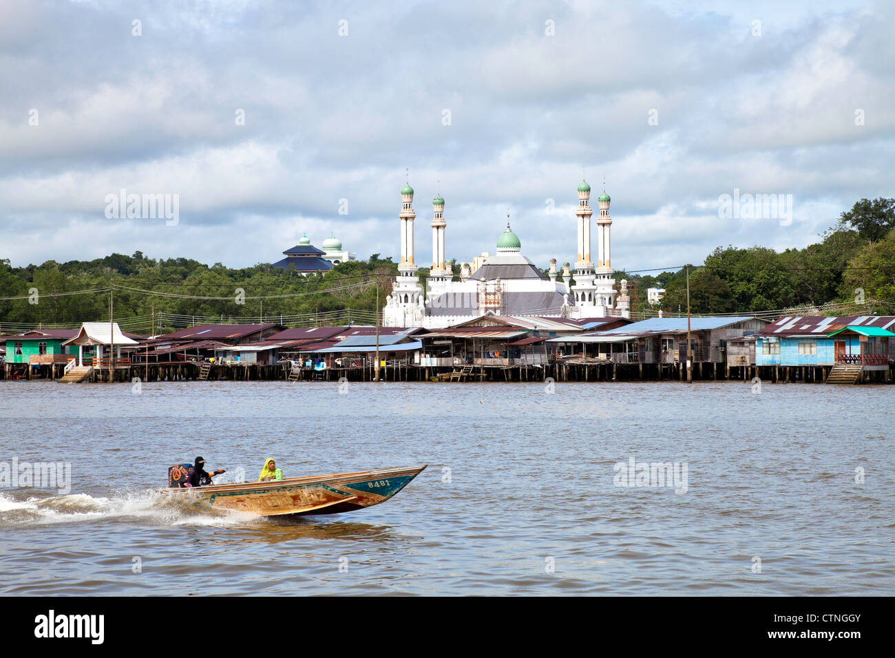 Water taxi with Kampong Ayer and a floating mosque in the background Bandar Seri Begawan Brunei. - Stock Image