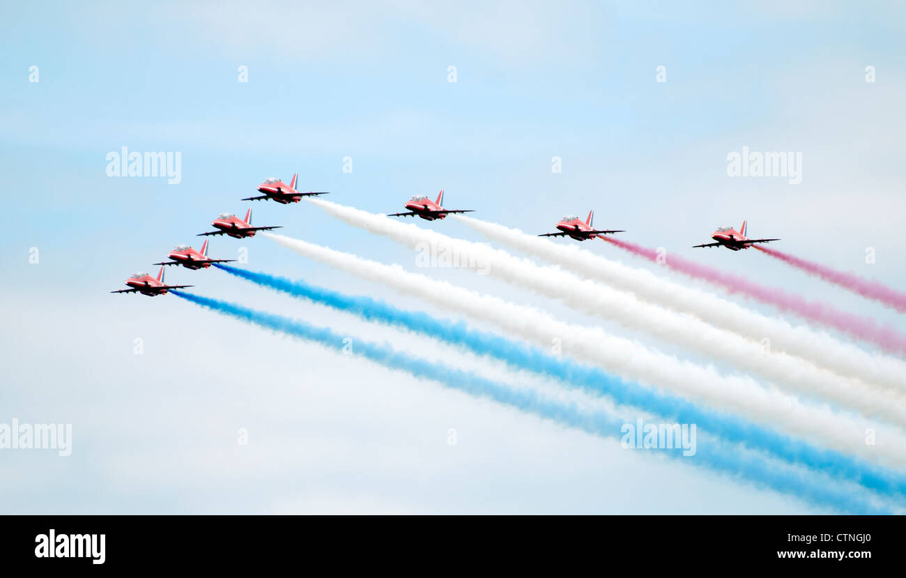 RAF Red Arrows display team trailing red, white and blue smoke Stock Photo