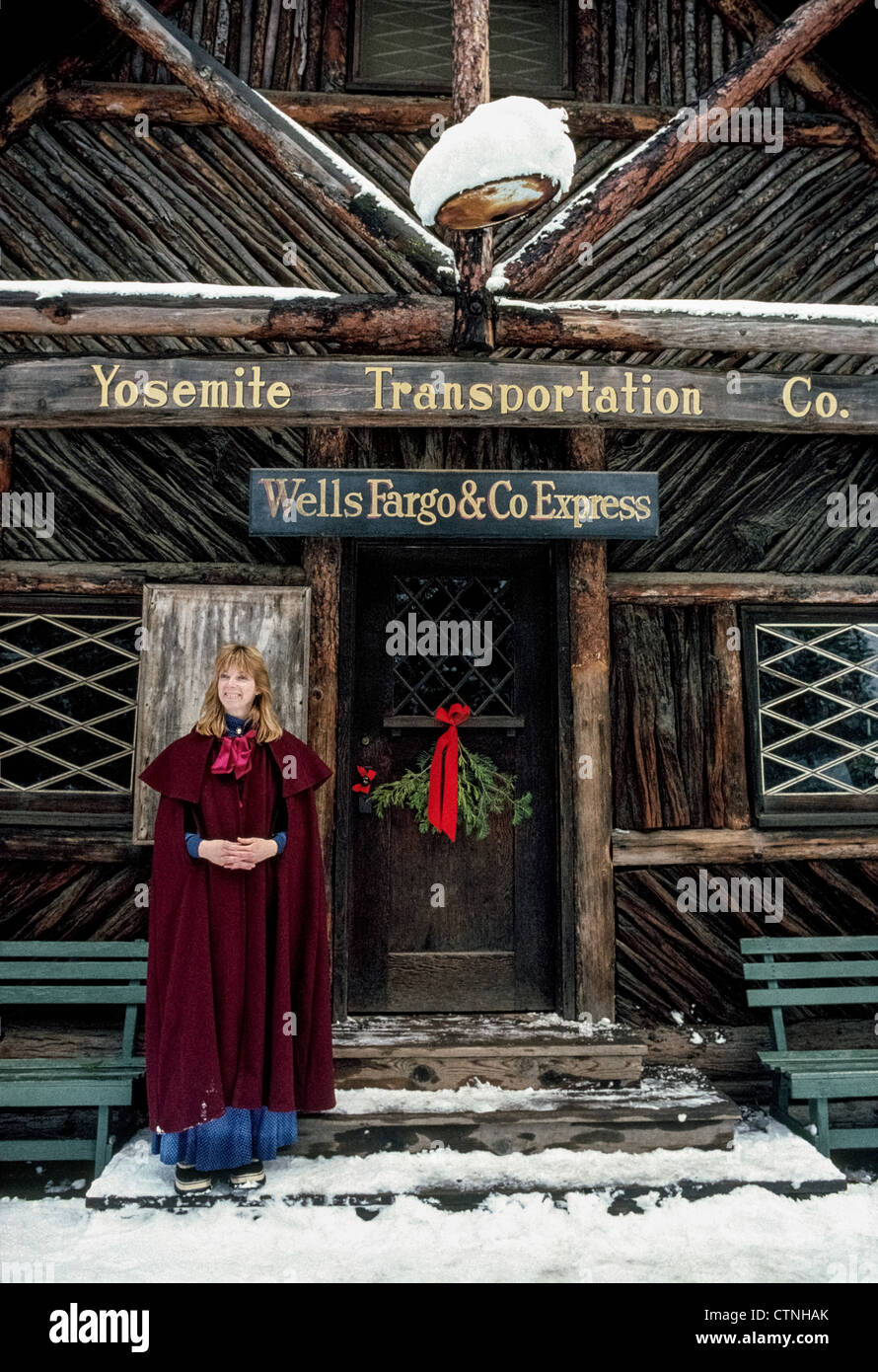 A Yosemite National Park hostess in early period clothing welcomes visitors at Christmastime to historic Pioneer - Stock Image