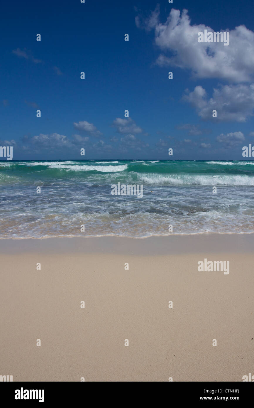 Small waves wash ashore at a perfect Caribbean beach under a clear blue Sky. - Stock Image