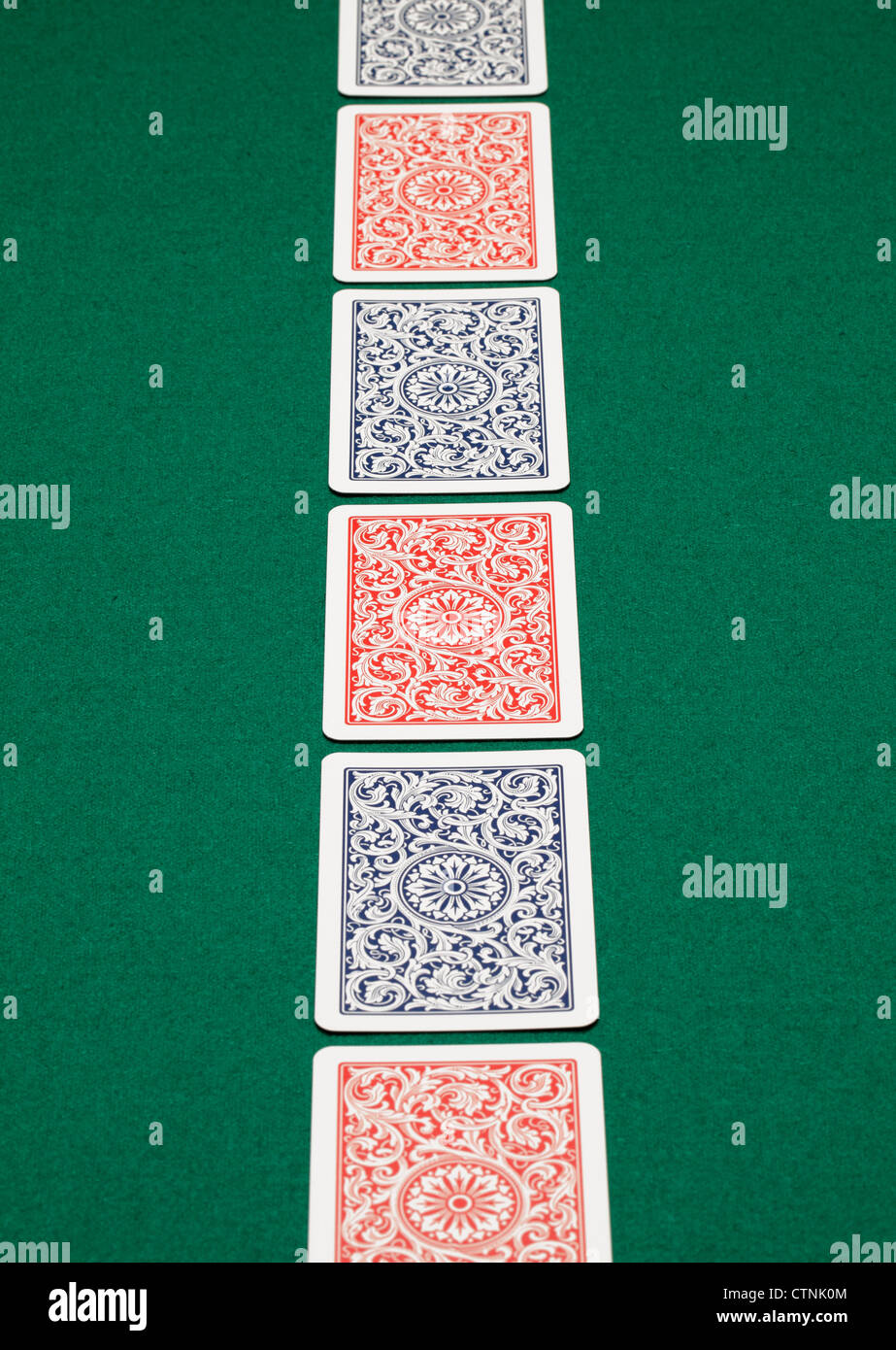 A line of playing cards on a green table. - Stock Image