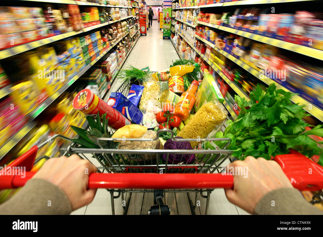 Food hall, full shopping trolley is pushed through a hallway with several food products. Large supermarket, self - Stock Image