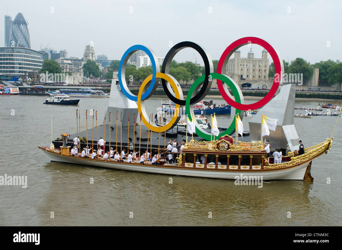 The Gloriana carrying the Olympic flame on the River Thames opposite The Tower of London London Uk London 2012 Olympics - Stock Image