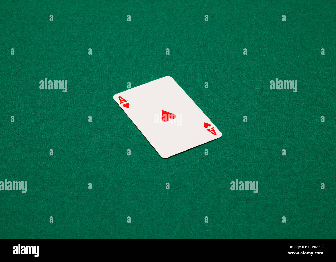 Playing card on a green table. The ace of hearts - Stock Image