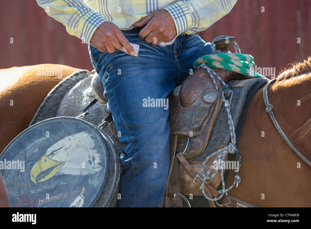 Native cowboy with a vintage western americana lariat lasso galvanized tin carry case in the warm-up arena at the - Stock Image