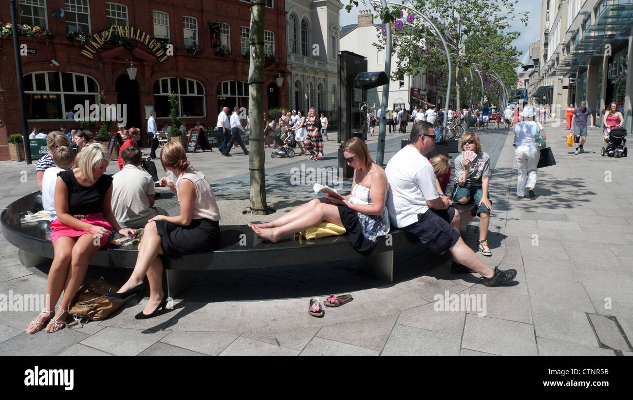 People relaxing on benches in Cardiff City Centre In the hot summer sunshine Wales UK  KATHY DEWITT - Stock Image