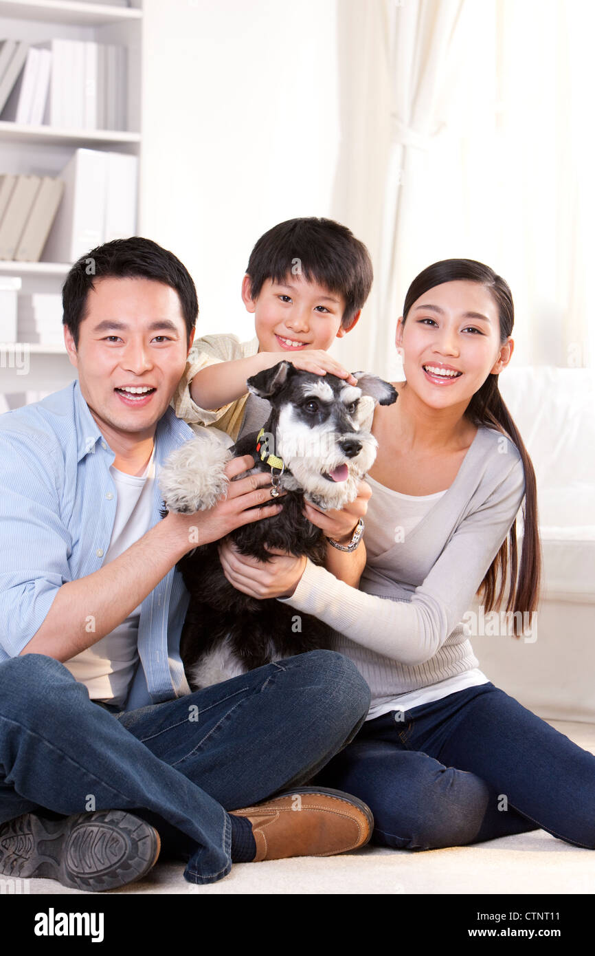 Happy family with pet schnauzer - Stock Image