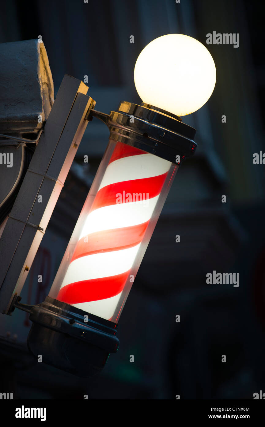 An old fashioned red and white striped barbers pole - Stock Image