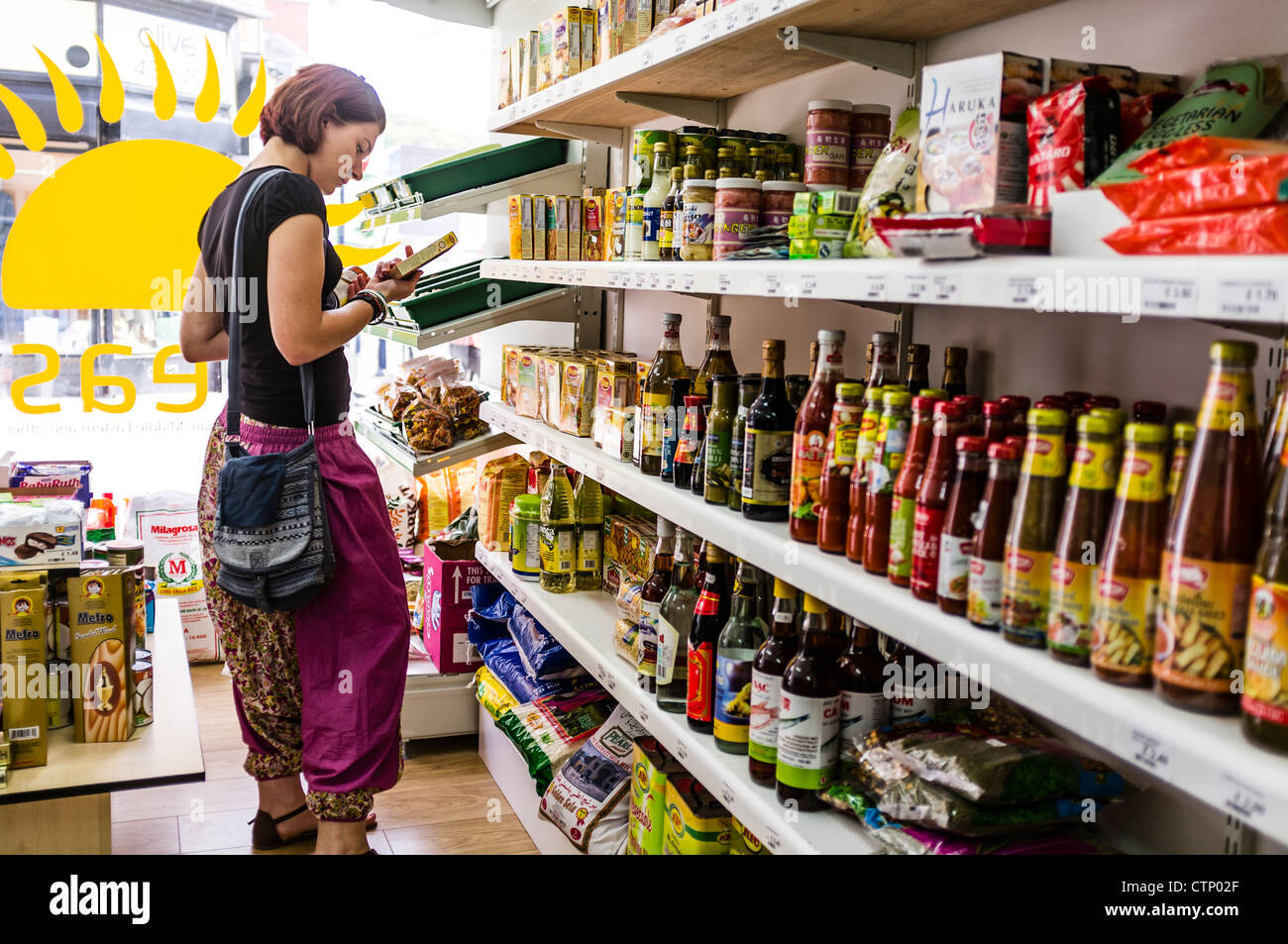 A young woman buying imported food at a delicatessen shop store , Aberystwyth Wales UK - Stock Image