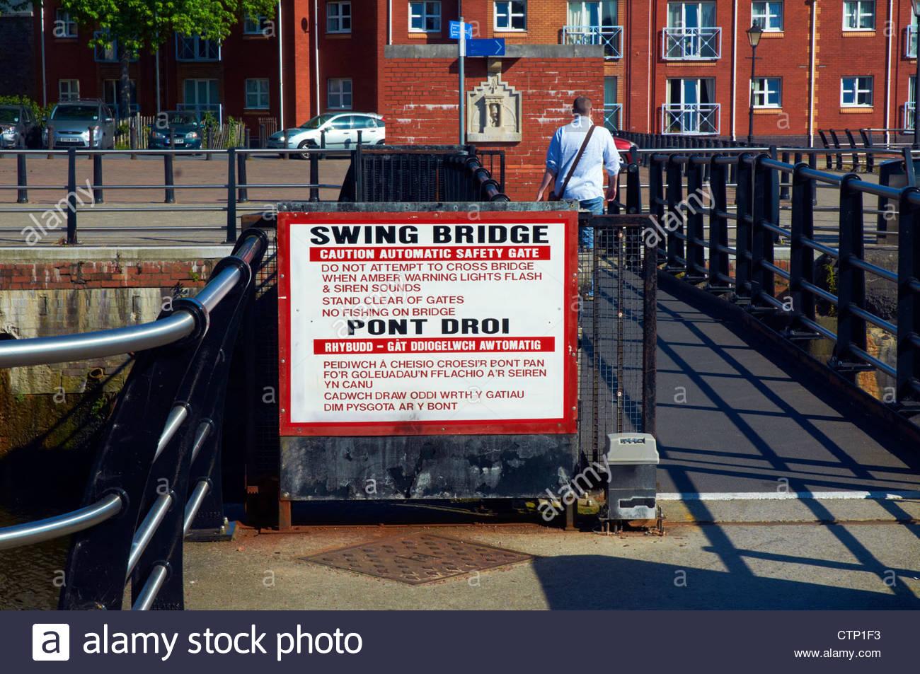 man walking on an automatic swing gate bridge in Swansea waterfront