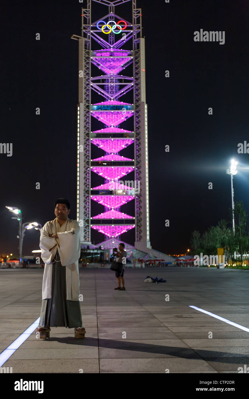 BEIJING CHINA - AUGUST 16, 2008: Chinese man in traditional dress poses in front of the Olympic tower with rings - Stock Image