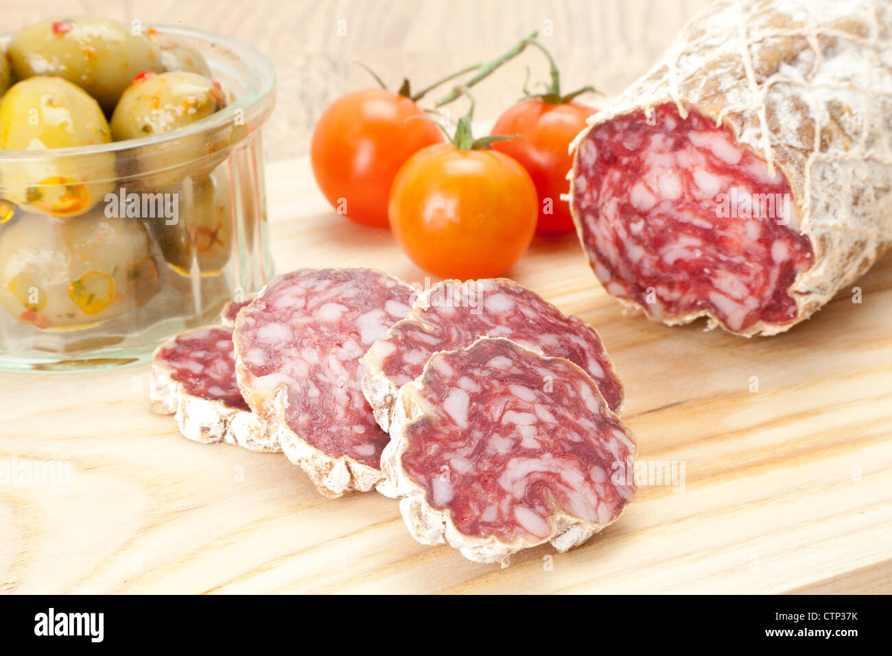 A dry cured salami sausage on a wooden cutting board with vine tomato's and olives in the background, shallow depth Stock Photo