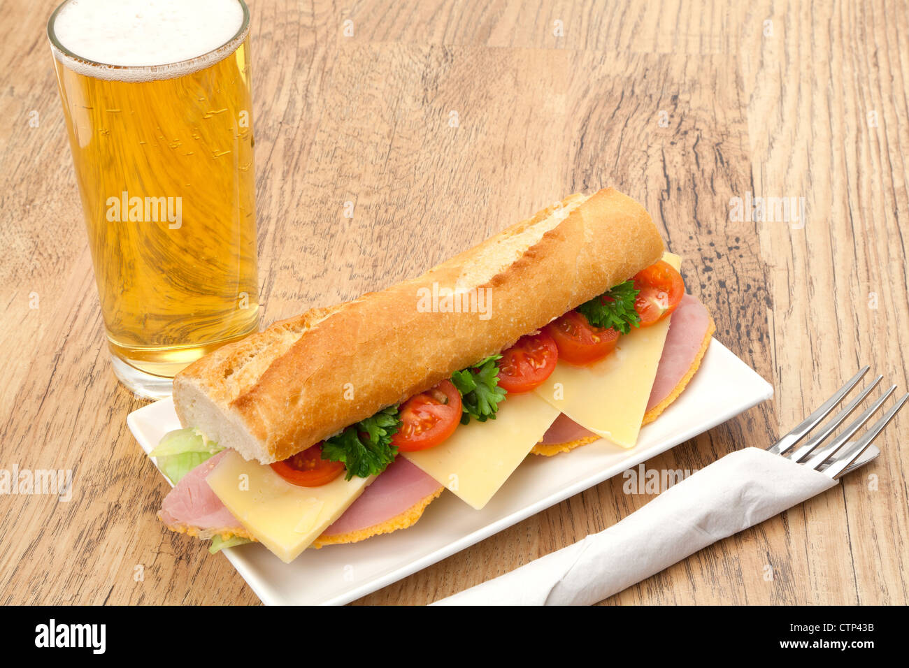 A traditional pub lunch of a ham, cheese and salad sandwich served in a slice of French baguette bread, accompanied - Stock Image