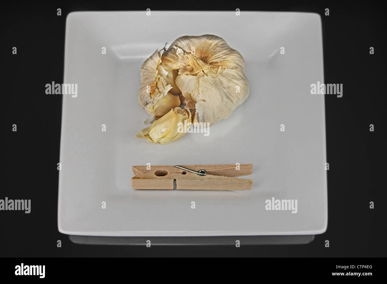 a square dish with cloves of garlic and a clothespin. The clothespin clamp is to hold your nose. Black reflective - Stock Image