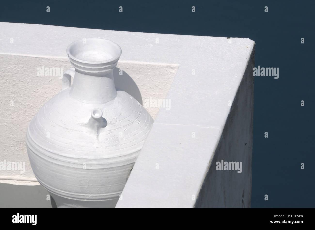 Darstellung einer Vase an einer Mauer auf einem Balkon eines Santoriner Hotels. - Stock Image