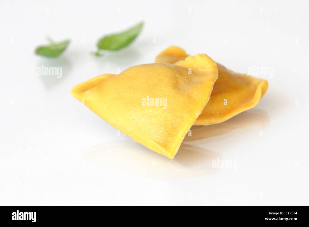 Fresh uncooked Ravioli (Stuffed Pasta) on white background - Stock Image