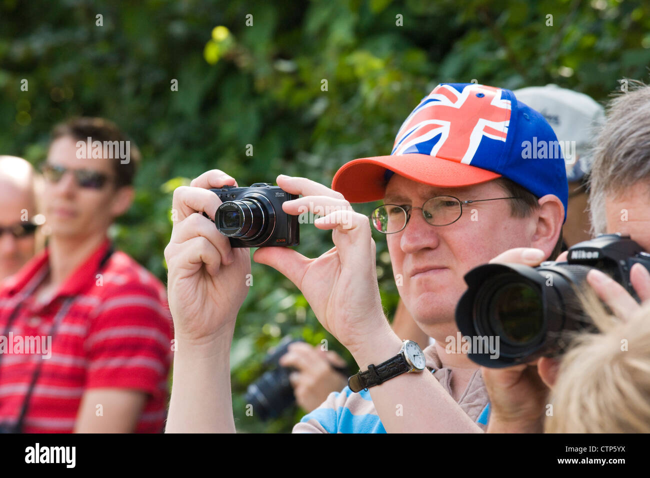 London 2012 Olympic Games. Spectators taking photographs of men's cycle road race at Ripley, Surrey. - Stock Image