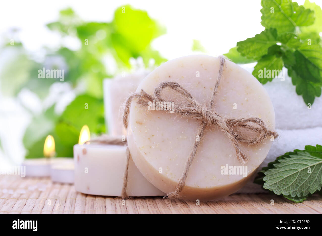 Bars of soap with fresh mint leaves and towels - Stock Image