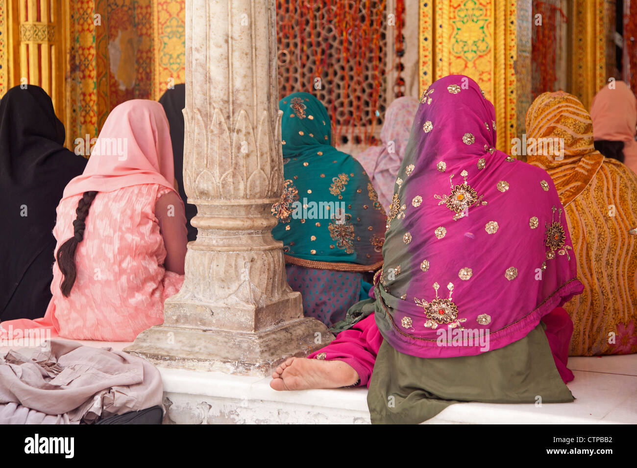 Muslim women wearing colourful headscarfs and saris praying at the Nizam-Ud-Din shrine in Delhi, India - Stock Image
