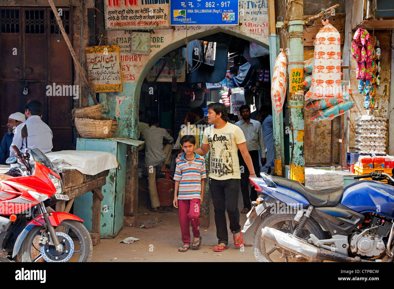 Pedestrians shopping in busy alley with stores selling goods on the street in Old Delhi, India - Stock Image