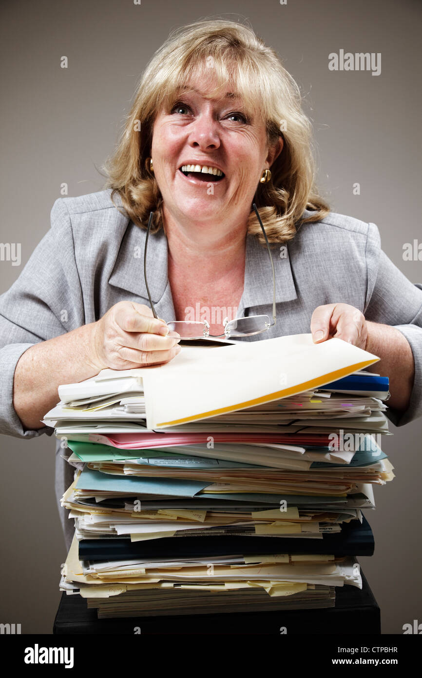 Mature woman losing it in demented laughter as work piles up - Stock Image