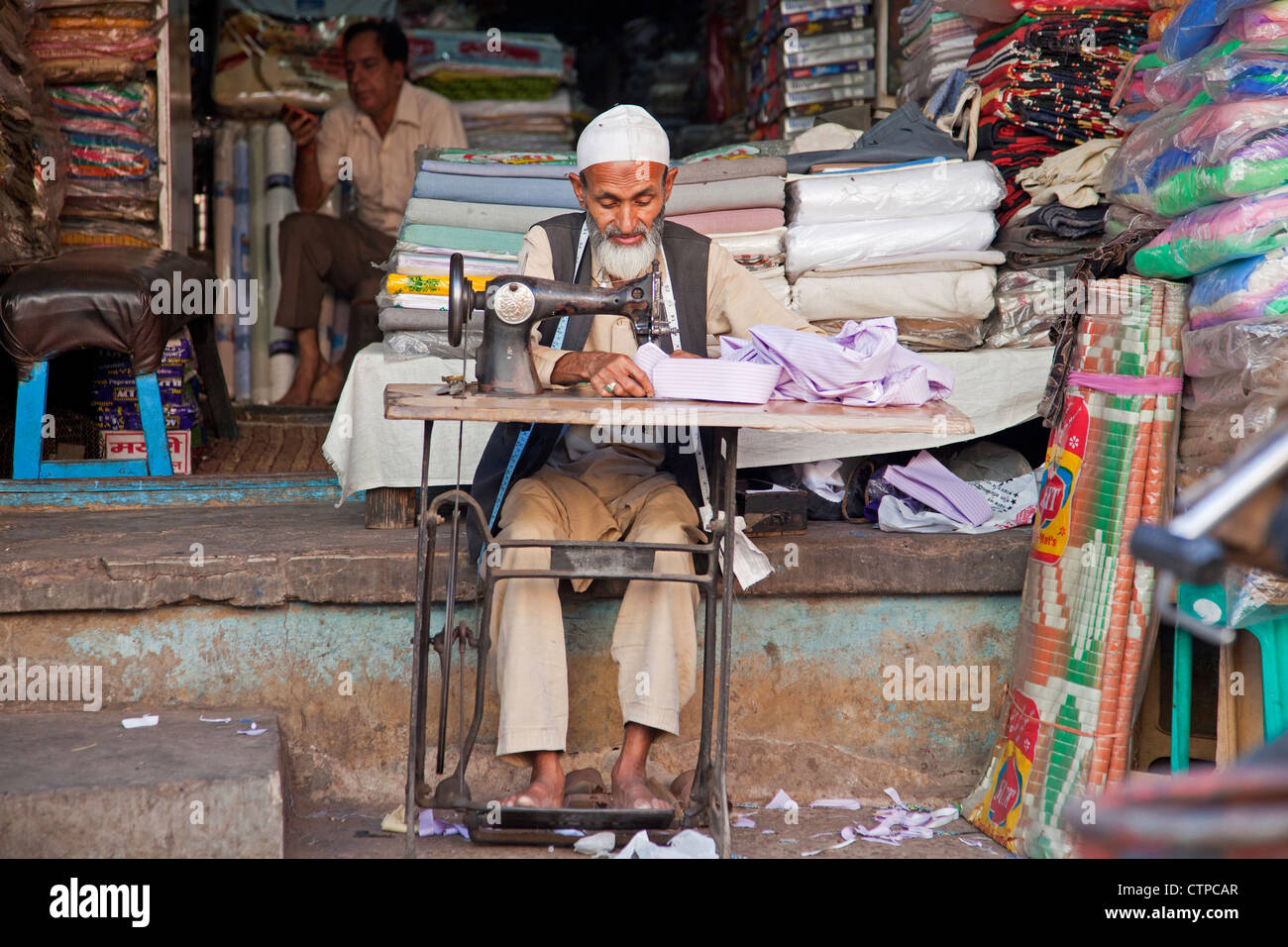 Tailor making clothes on old sewing machine in front of tailoring establishment, Delhi, India - Stock Image