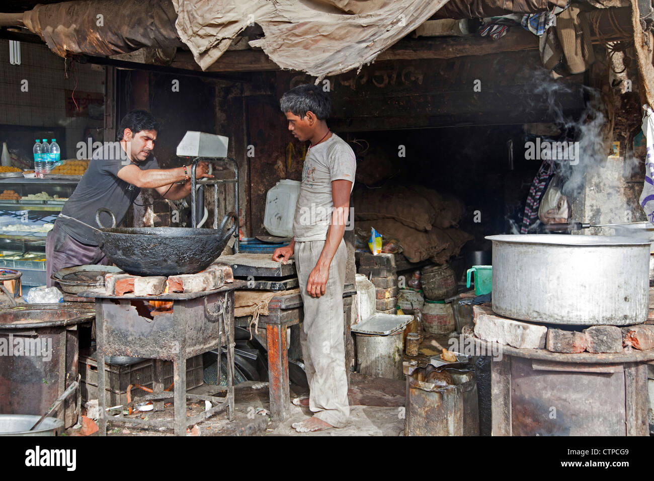 Men cooking food in dirty unsanitary primitive kitchen in Mathura, Uttar Pradesh, India - Stock Image