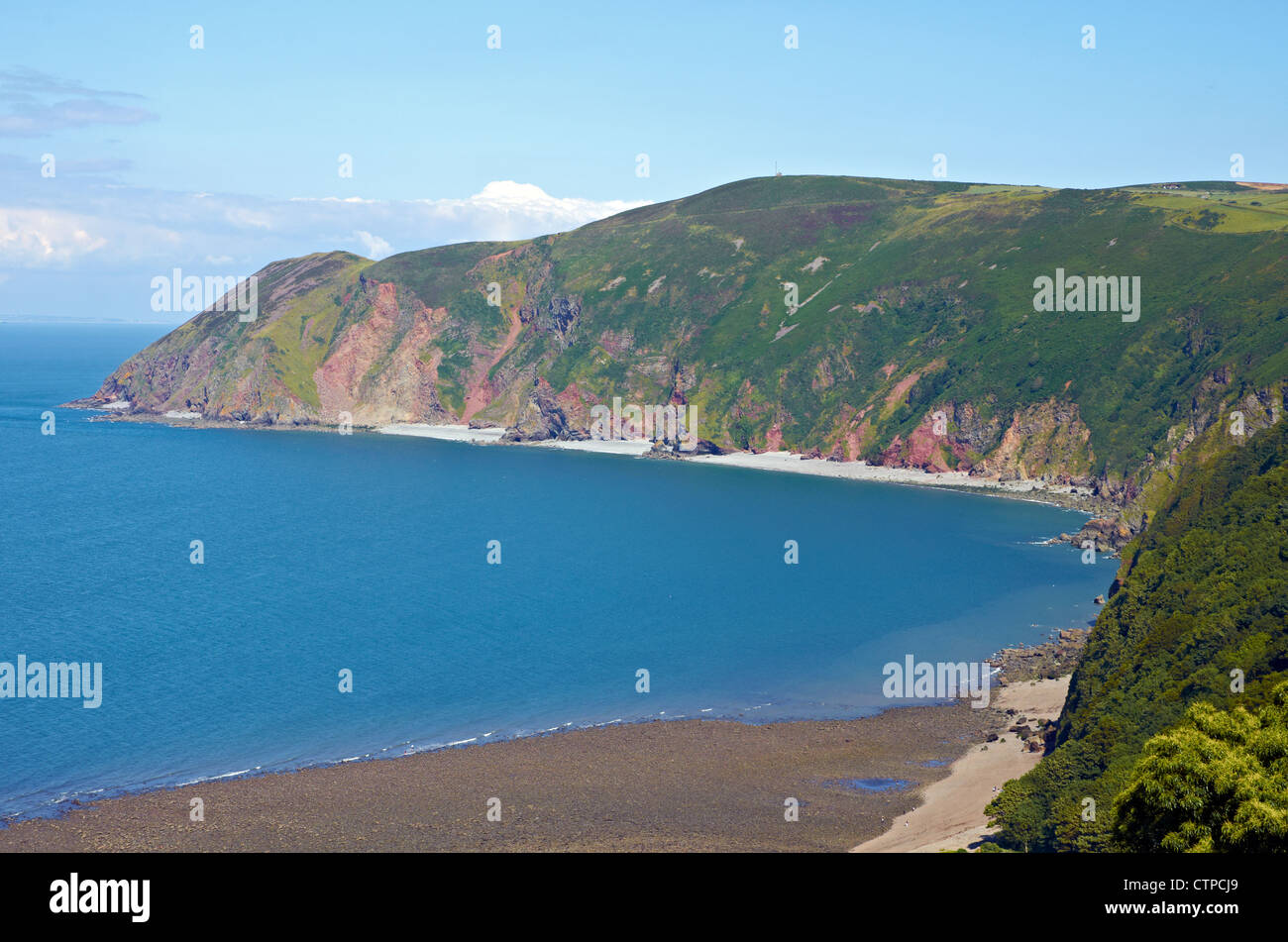 Beach at Lynton, Devon showing rocky and stony nature with steep Old Red Sandstone cliffs and Exmoor moorland seen - Stock Image