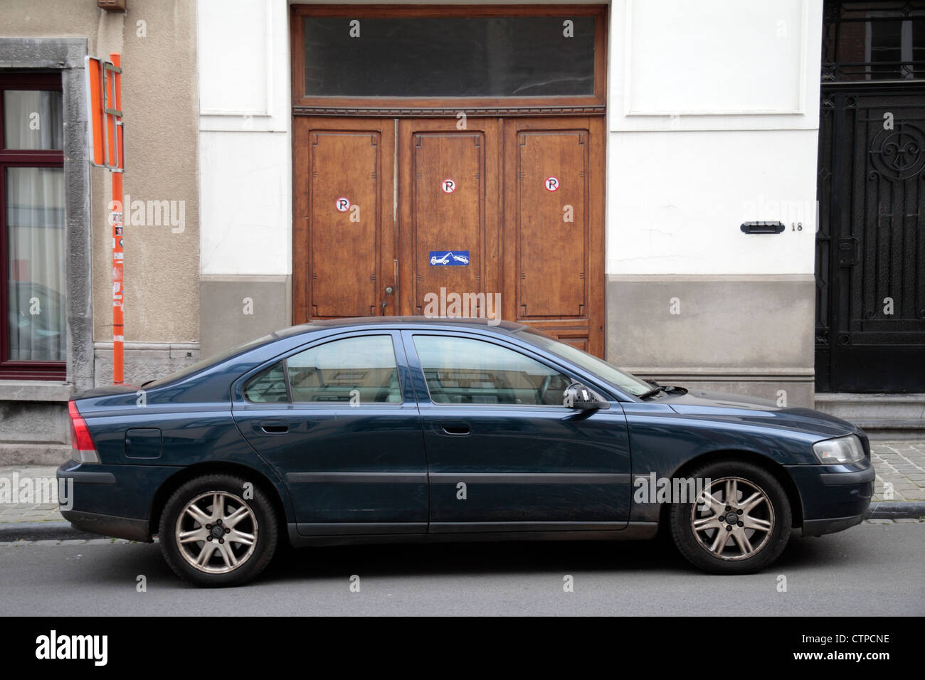 Car blocking an entrance with a sign warning the parked cars will be towed in  Mons, Wallonia, Southern Belgium. - Stock Image