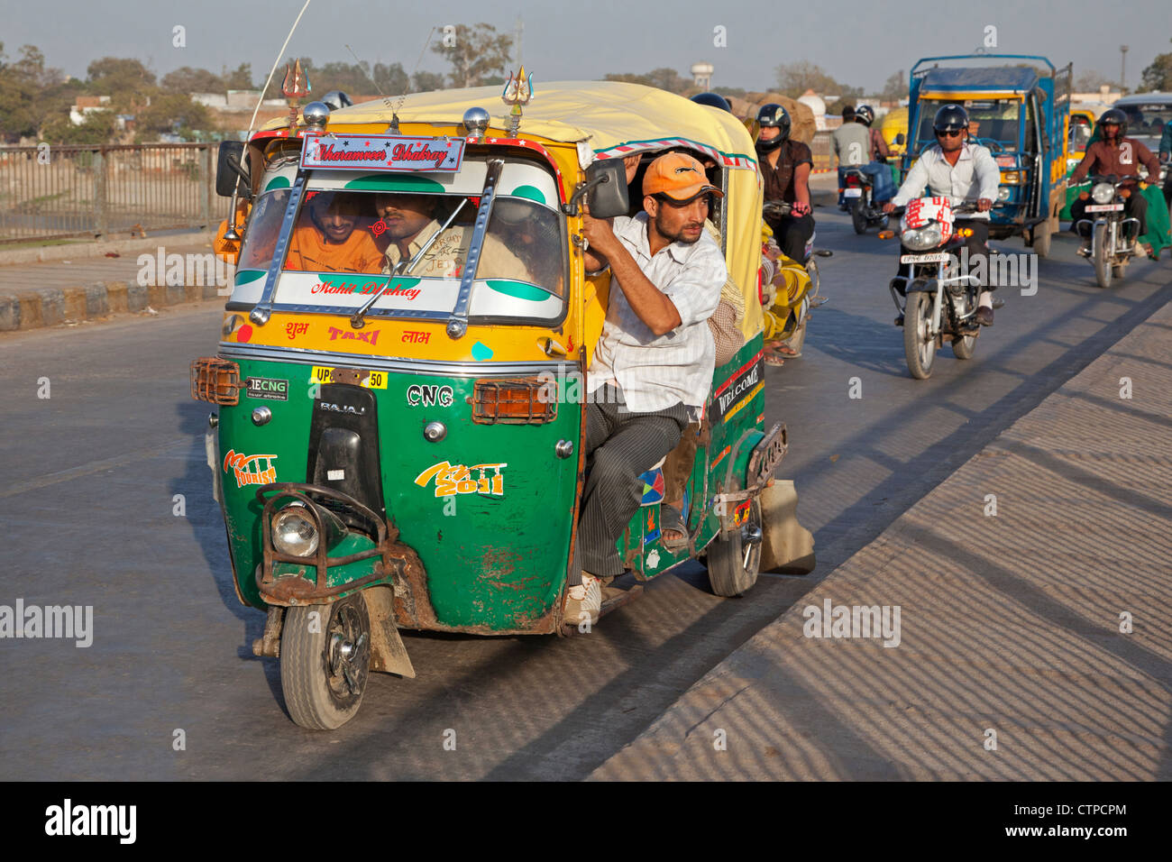Fully loaded autorickshaw, three-wheeled motorized taxi in busy traffic at Agra, Uttar Pradesh, India - Stock Image