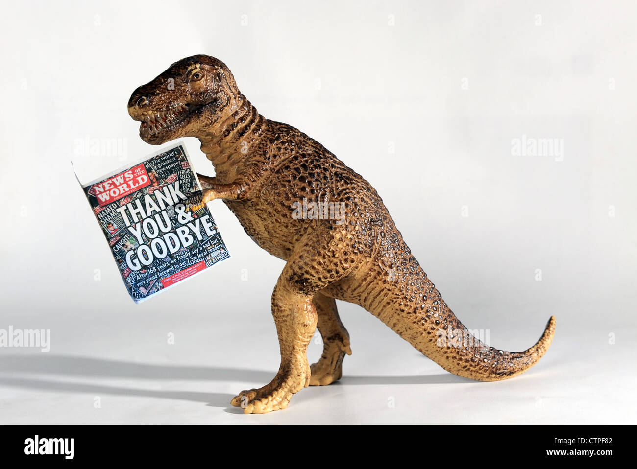 News of the World newspaper held by toy dinosaur Stock Photo