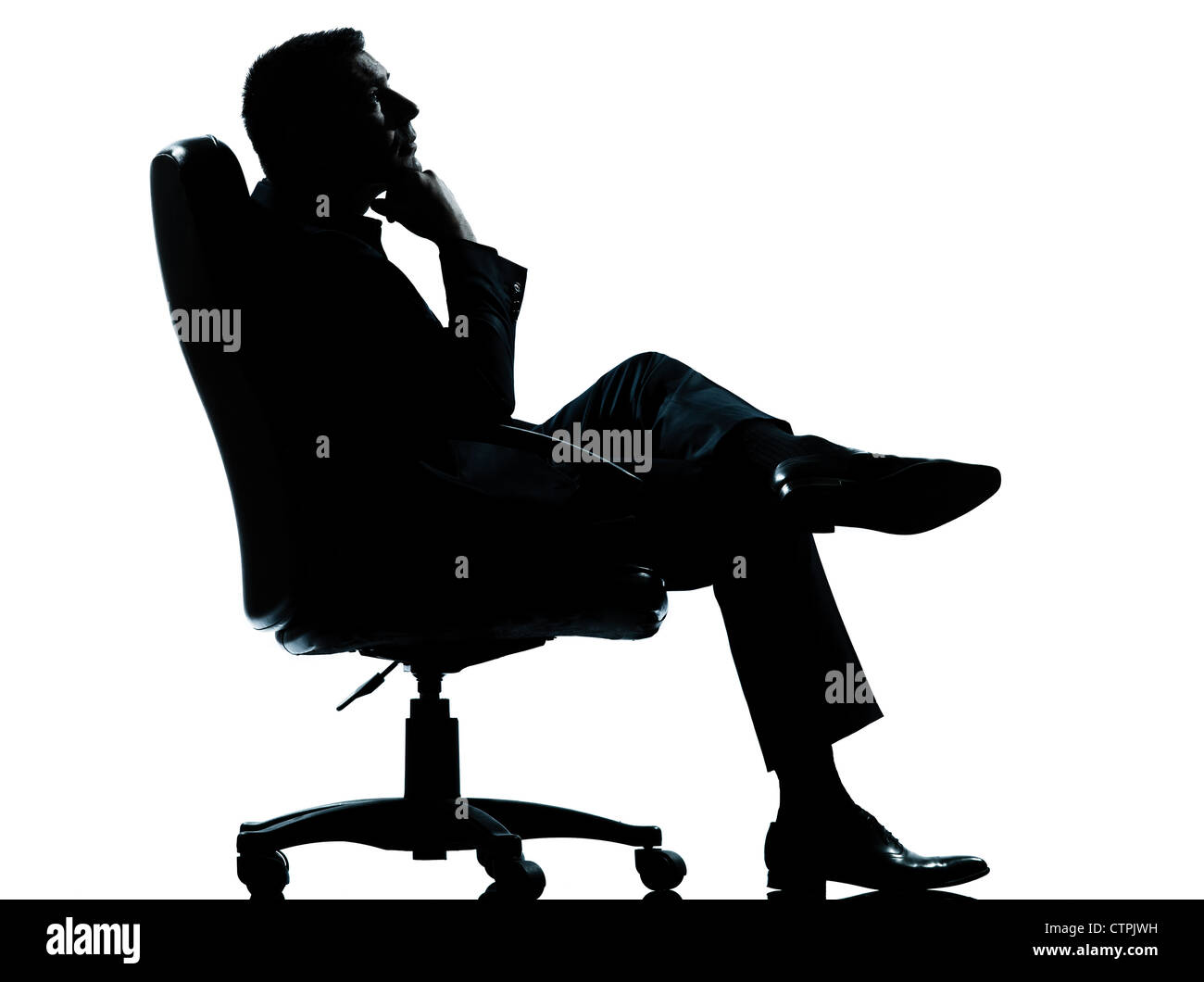 one caucasian business man relaxing thinking sitting in armchair silhouette Full length in studio isolated on white - Stock Image