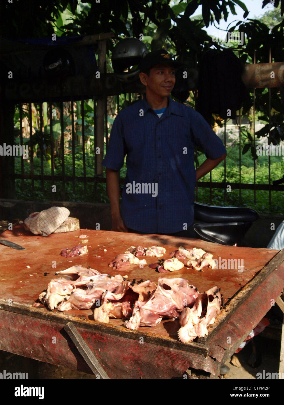 stall holder with raw chickens covered in flies on sale at an open air street market in jakarta indonesia Stock Photo