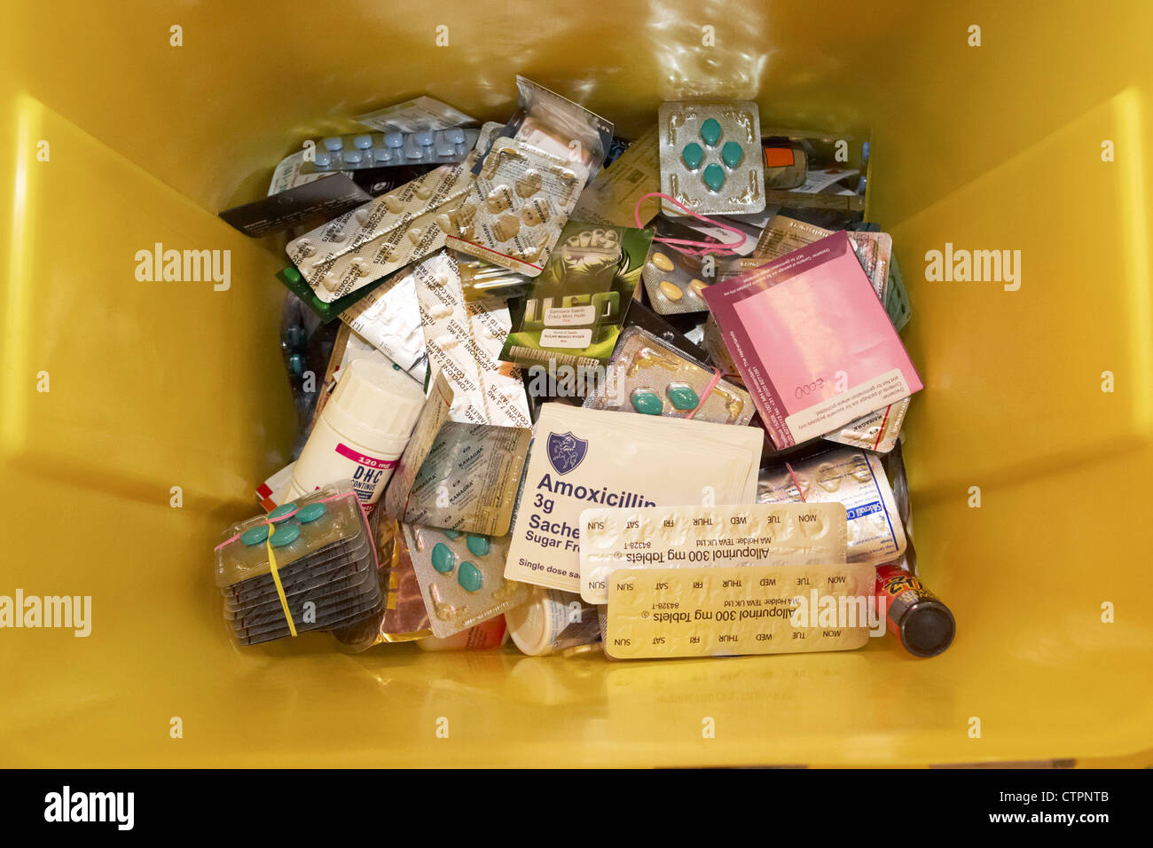 discarded tablets and drugs in a yellow container for disposal confiscated from mail post system - Stock Image