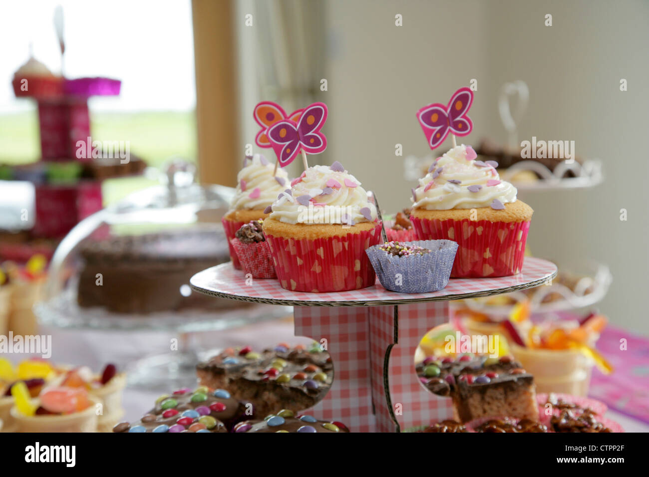Decorated Cup Cakes On A Stand With Food And Drink Laid Out Table For Young Girls Birthday Party