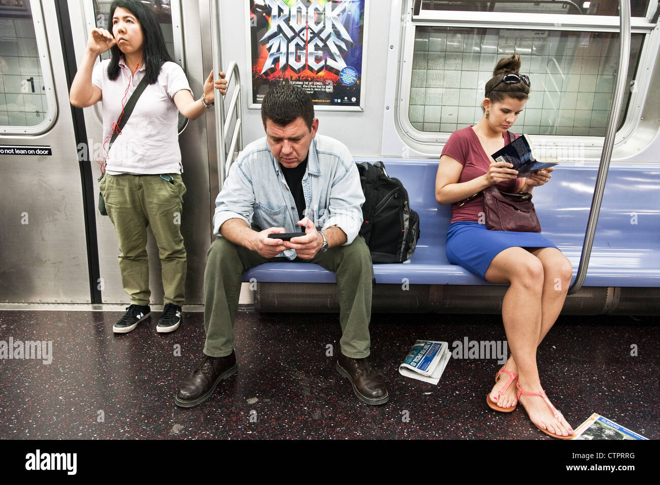 3 self absorbed New York subway passengers, a man & 2 young women, each absorbed in a private world reading - Stock Image