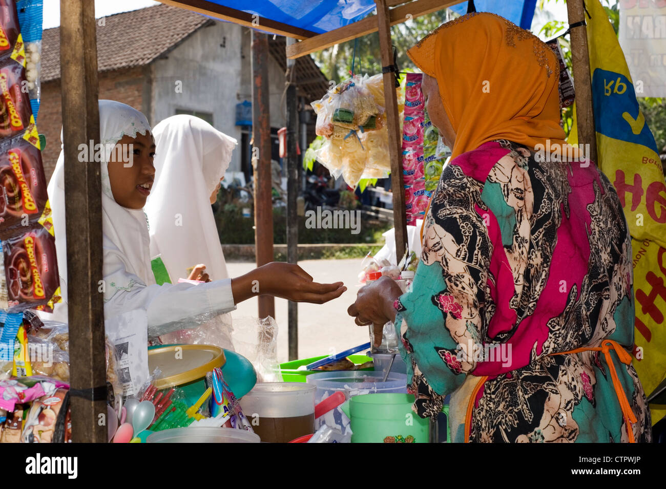young muslim schoolgirl buying snacks at stall during break time java indonesia Stock Photo