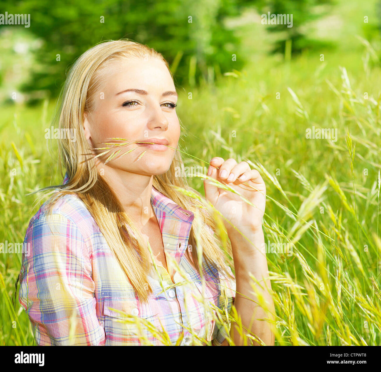Cute blond girl on wheat field, woman sitting on green grass, female relaxing outdoor, happy pretty teen girl holding Stock Photo