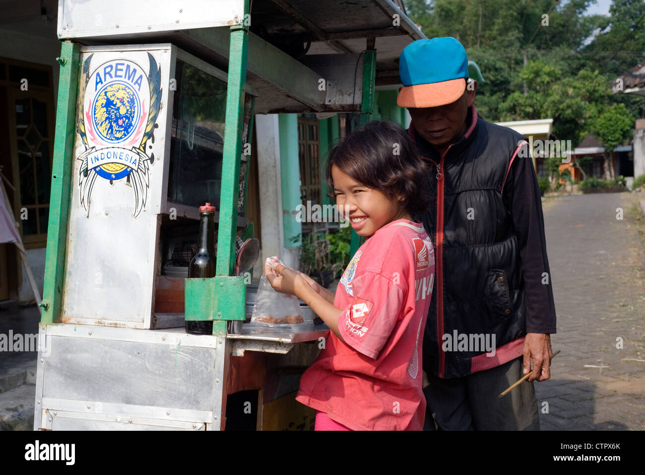 young village girl buying traditional bakso snack from sellers cart in rural village street java indonesia Stock Photo