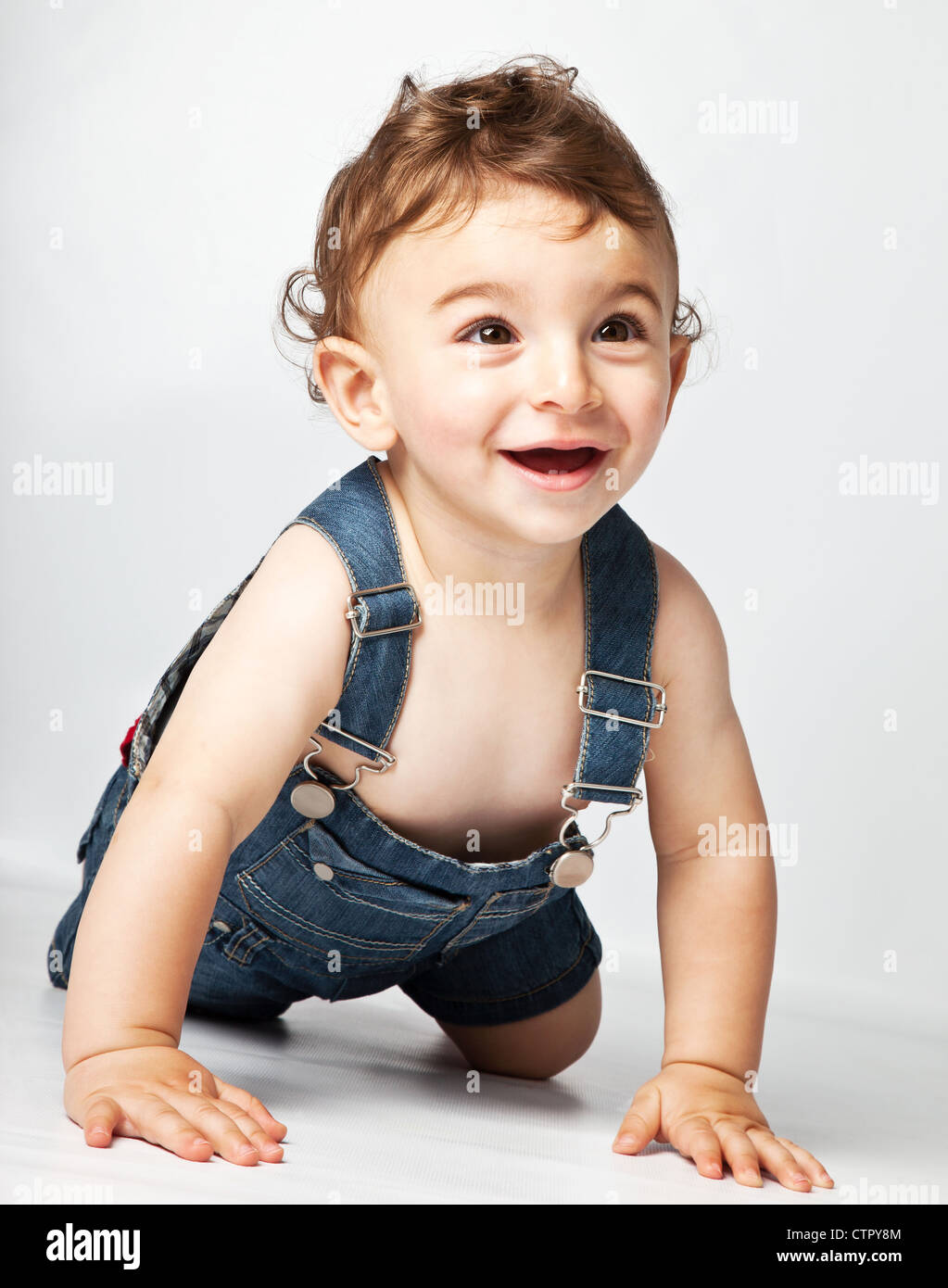 happy baby boy creeping on studio floor, beautiful cute cheerful kid