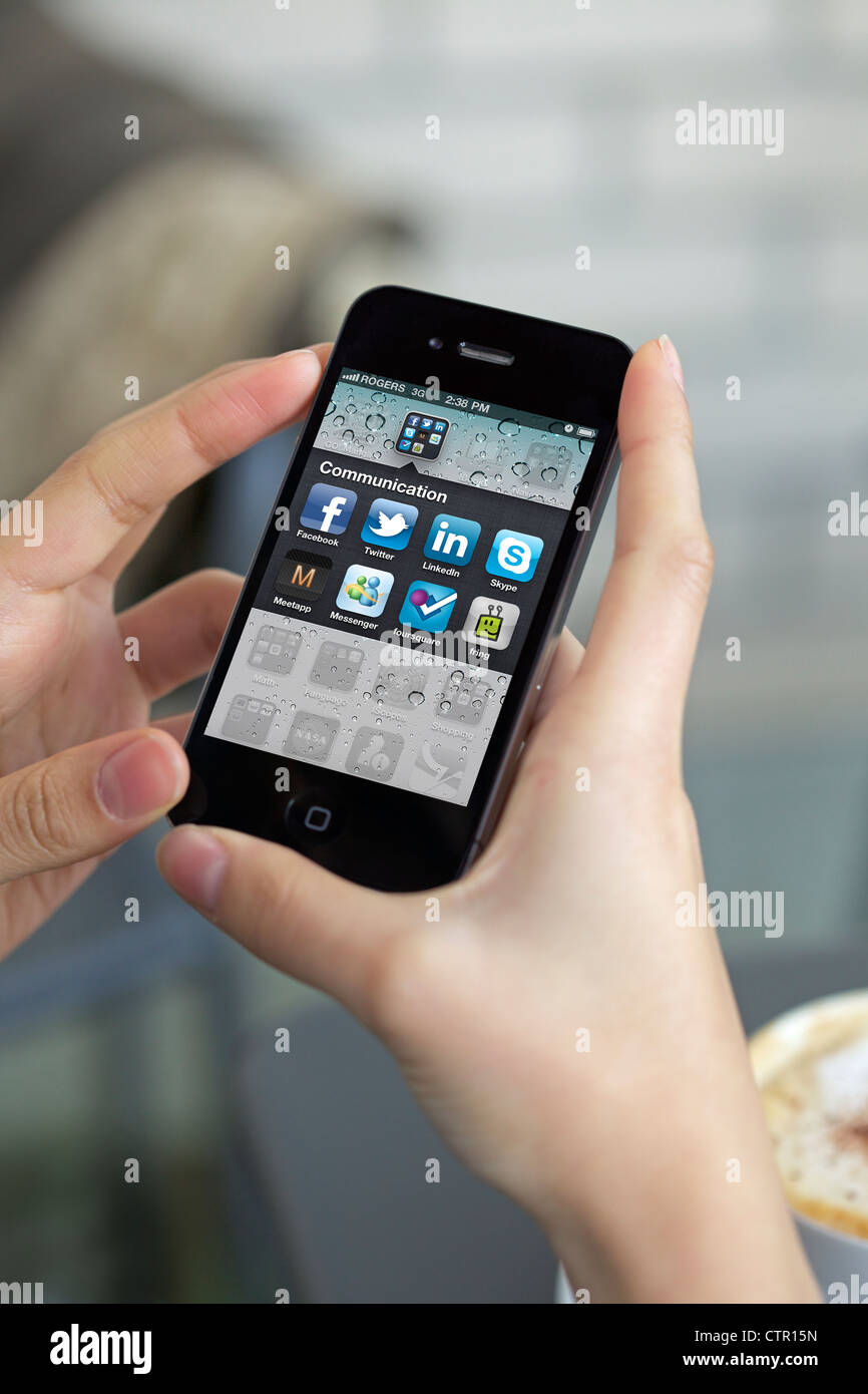 Close up picture of a woman hand holding an iPhone 4 showing the new iPhone (retina display/300 DPI) application Stock Photo