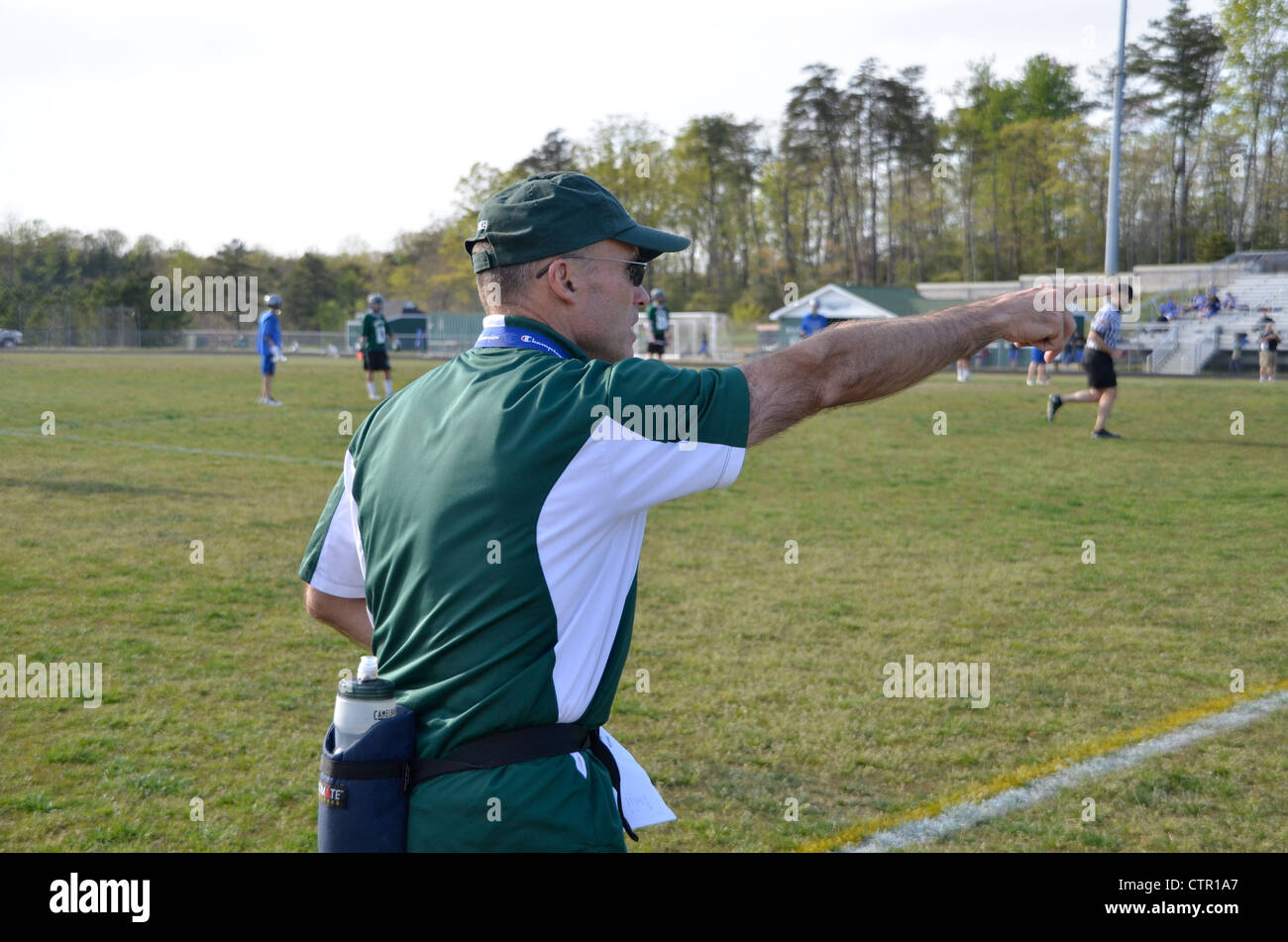 coach yelling instruction from the sidelines in a high school lacrosse game - Stock Image