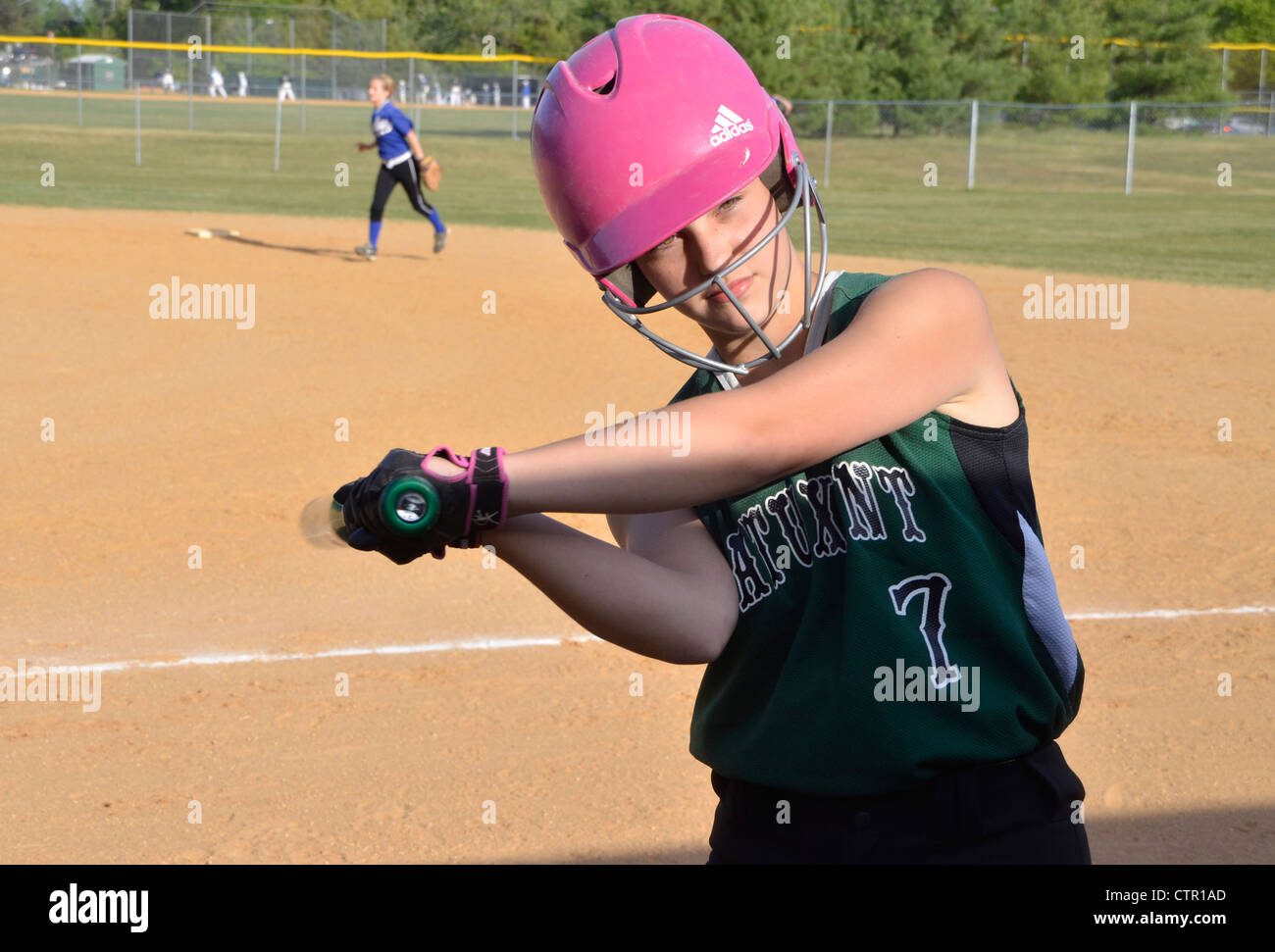 A female softball batter takes some warmup swings before she comes up to bat - Stock Image