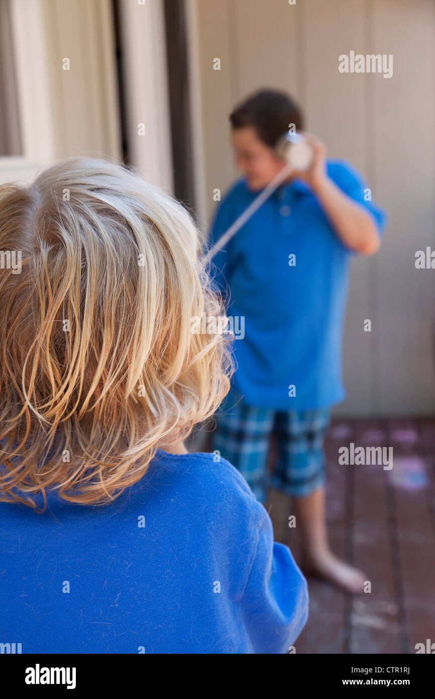 Two boys talking by a string and can telephone. - Stock Image