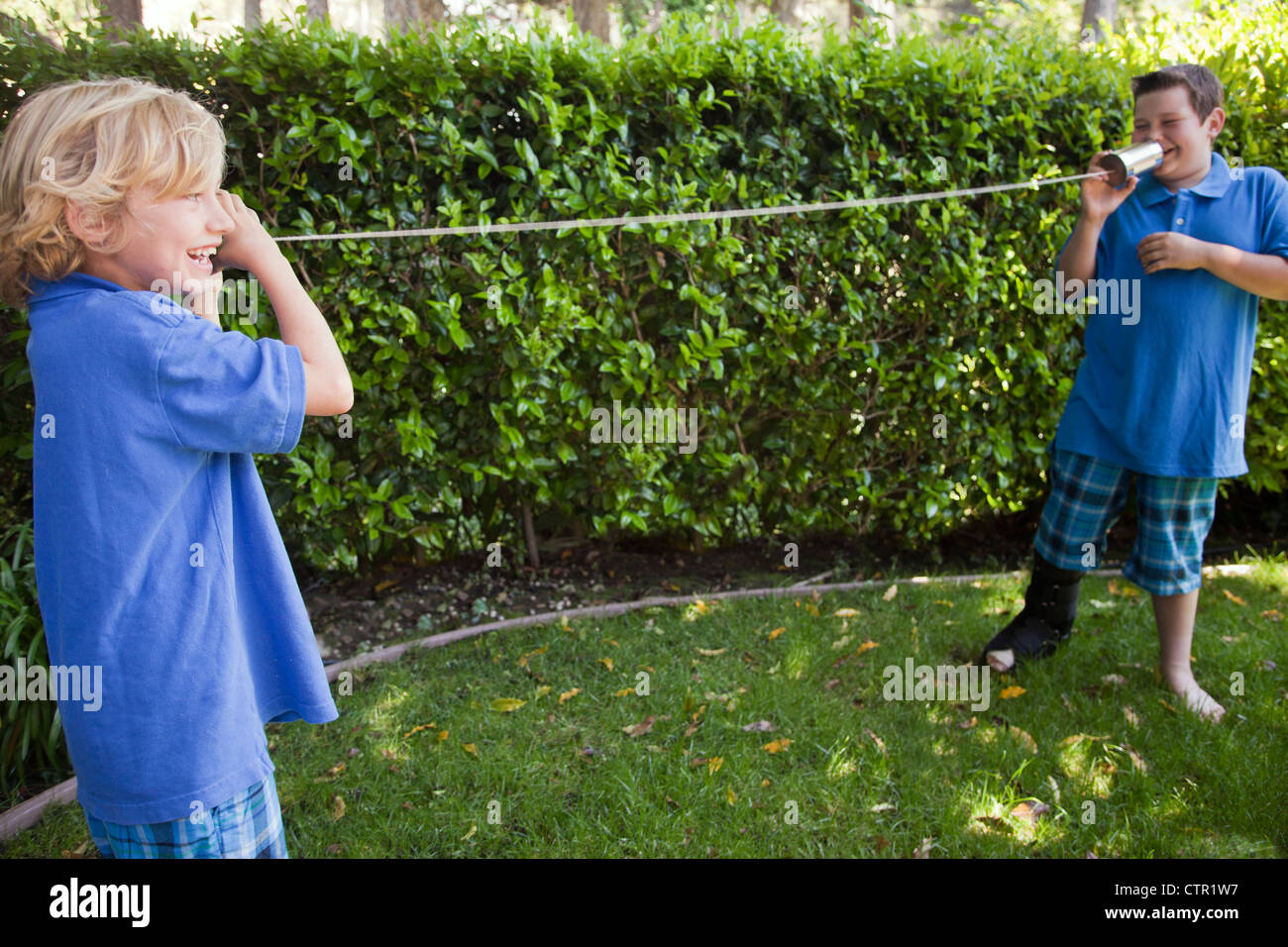 Two brothers talking on a can and string telephone. - Stock Image