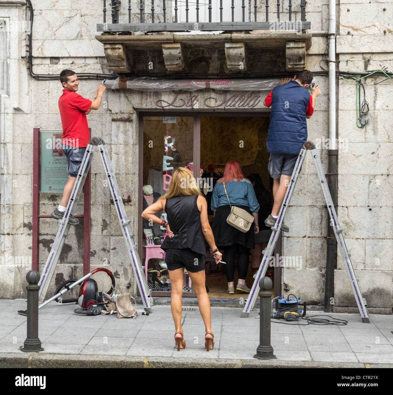 Woman in high heels smoking a cigarette watching men work outside shop in Spain - Stock Image
