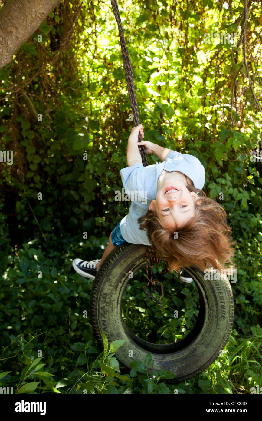 A little girl swinging from a tire swing. - Stock Image