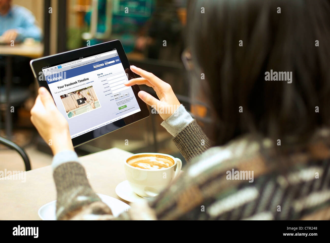 Close up view of female handholding an ipad logging in to her stock close up view of female handholding an ipad logging in to her facebook account ccuart Image collections