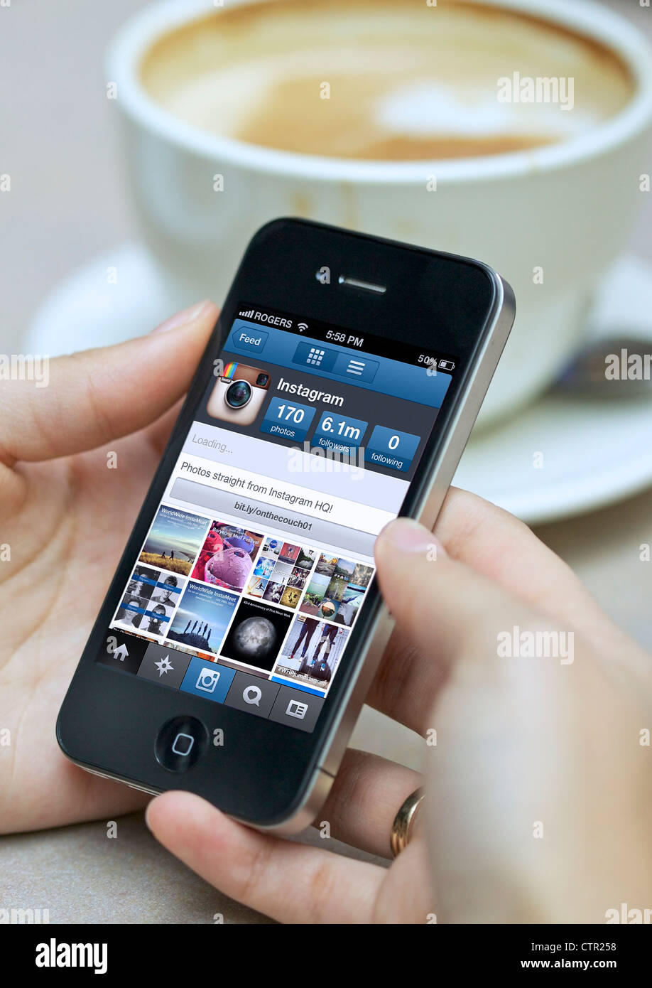 Close up picture of woman handholding an iphone using Instagram camera app - Stock Image